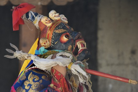 Buddhist Lama in the ancient blue Mask Monster with a trident in his hands, a feast in a Tibetan monastery. Stock Photo