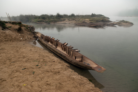 Wooden boat with inverted seats near the river bank, early morning, Chitwan, Nepal.