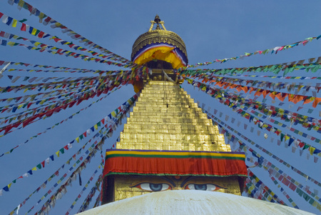 Top of the Buddhist stupa Bodnath: the golden dome and the Buddhas eyes beneath it, the prayer Tibetan flags in different directions diverge against the blue sky background, Kathmandu, Nepal. Stock Photo