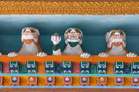 Sculptures of three stone snow lions among Tibetan ornaments in a Buddhist monastery, Sikkim, India.