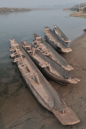 Native long wooden canoes with upturned chairs on the bottom stand on the river bank, in the background one can see the opposite shore, Nepal.