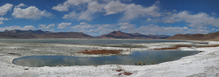 Turquoise lake among the high mountains salt desert, mountain hills in the background, in the blue sky clouds, the Himalayas, panorama. Stock Photo