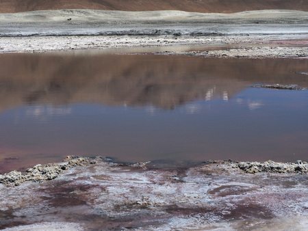 Abstract background of the land texture of the shore of the lake, a strip of lake water with reflections and deposits of stone salts on the far shore. Stock Photo
