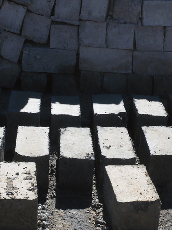 Bricks are handmade laid out on the ground to dry, in the background a wall of dried bricks.