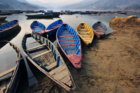 Wooden boat, red, blue and yellow on the earthy shore of a mountain lake. Stock Photo