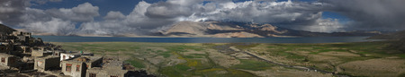 Karzok village and high mountains of Lake Tz Moriri, turquoise water, ridges in the background, on the front floodplain of the river with green fields, photo panorama, Tibet, Himalayas, India.