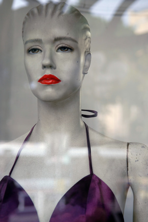 Dummy mannequin through the glass showcases: a white high doll with bright red lips, a displeased face. Stock Photo