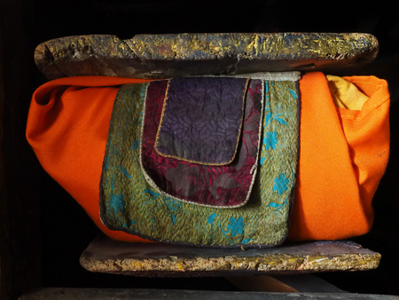 Traditional ancient Tibetan book: the texts are wrapped in orange cloth, on top and bottom are thick wooden plaques, Buddhist religious texts.