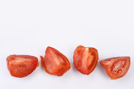 Red juicy lobules of fresh tomato lie in a line on a white background, on top of the free space for text. Stock Photo
