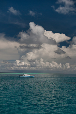 Small white boat in the middle of the purest turquoise ocean water under the sky with beautiful white cumulus clouds, vertical frame.