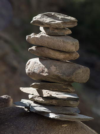 Small Buddhist stupa, composed of hands of flat brown boulders of different sizes. Stock Photo