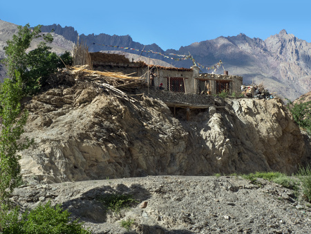 Traditional Tibetan house in a mountain village on the rocks among the greenery, Tibet.