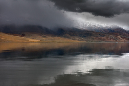 Thunderstorm on the mountain lake: black clouds thicken above the mirror of the water, white chains of mountains peep out of the clouds, mountain slopes are painted yellow in the sun.