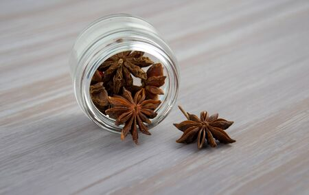 Asterisks fruit anise in a glass jar, inverted, lies on its side on a wooden table surface.