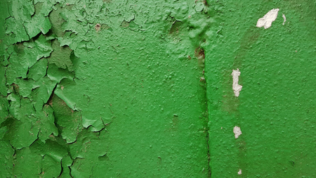 Abstract background of a metal wall, covered with green paint, in some places the paint disappears, on the left small white spots of paint.