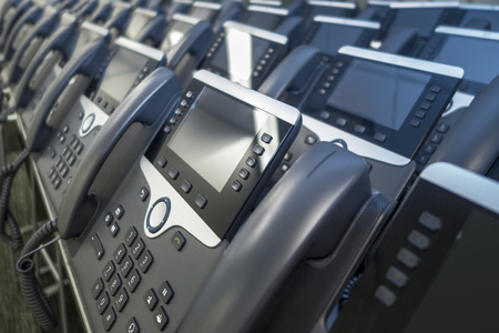 Lots of IP eithernet phones in rows ready to be used by employees