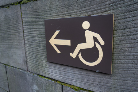 arrow and wheelchair icon sign on wall in an anagle view