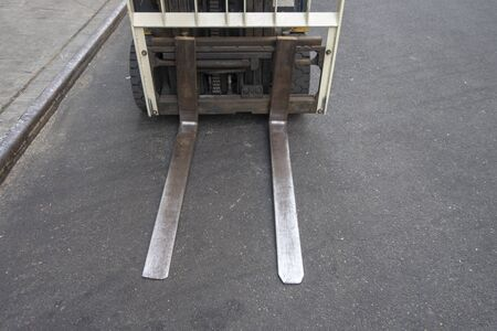 close up of a shipping transportation fork lift blades on a city street asfalt