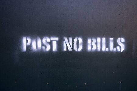 Post No Bills spray painted on green plywood around a contrution sight