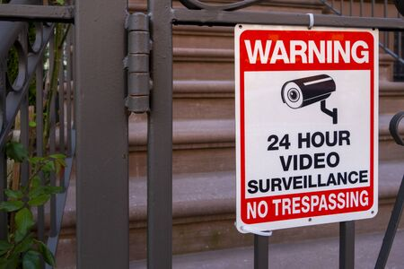 """red white and black safety security sign with camera icon and test that read """"warning 24hour video surveillance no trespassing"""