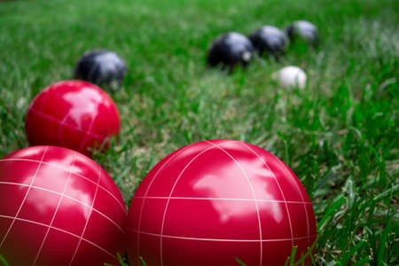 Red and dark blue bocci balls on a green grass lawn playing the game