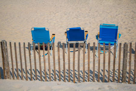 blue folding chairs on a sandy beach with wood vertical fencing