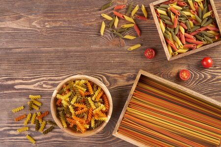 Multicolored pasta on wooden background with copyspace and bag Stock fotó
