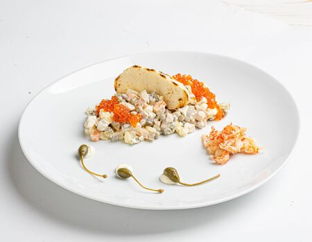 Olivier salad with capers on white plate Standard-Bild