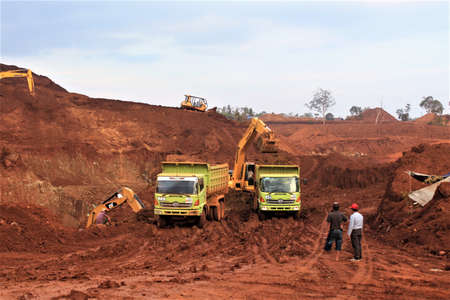 Pomalaa, Indonesia - June 19, 2011: Open nickel mining activity by clearing land using heavy axle excavators