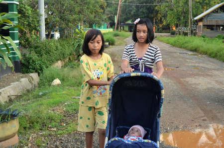 Kolaka, Indonesia-November 12, 2011: Little girls pushing prams 新闻类图片