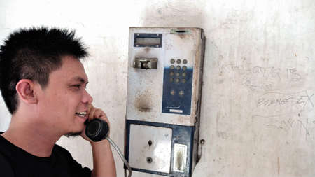 Jakarta, Indonesia-October 24, 2018: A young man uses a public telephone 新闻类图片