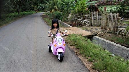 KOLAKA, INDONESIA - November 25, 2018: A girl is riding a toy motorbike on the highway