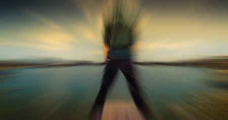 waddling: A boy standing on a end of lake shot with motion blur effect.