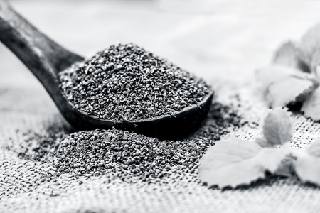 Trachyspermum ammi, Ajwain seeds in a wooden scoop with some leaves on a gunny background. Stock Photo