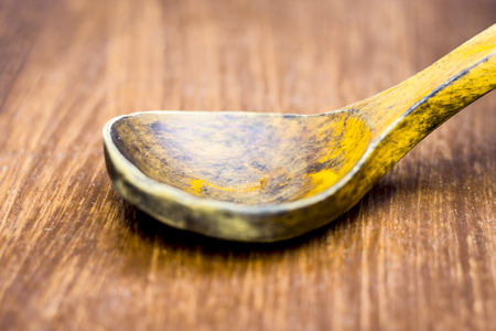 Yellow colored wooden scoop on the wooden surface.