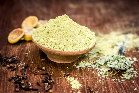 Raw powder of Henna,Lawsonia inermis in a clay bowl with lemons and cloves. Stock Photo