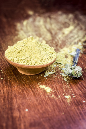 Raw organic powder of Henna,Lawsonia inermis in a clay bowl with its dry leaves on wooden surface. Stock Photo