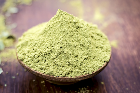 Raw organic powder of henna,Lawsonia inermis in a clay bowl on wooden surface.