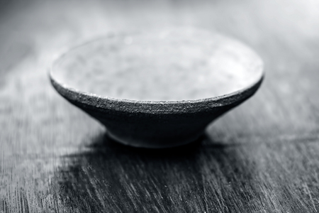 Brown colored clay bowl,mud utensil on wooden surface. Stock Photo