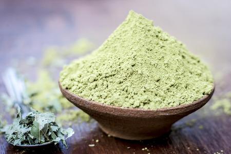ヘナの生の有機粉末、ローソンニアは、木製の表面に乾燥した葉を持つ粘土ボウルにイナーミス。