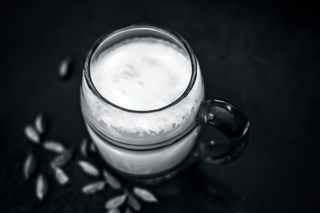 Sweetened milk with some green cardamoms on brown wooden surface. Reklamní fotografie