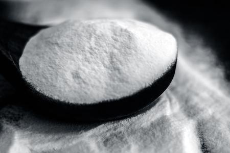 bicarbonato de sodio o cúrcuma en polvo de sodio en una cuchara de madera en la superficie de madera marrón .