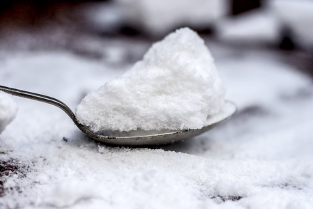 Common salt, Sodium chloride in a wooden scoop on wooden floor. 스톡 콘텐츠