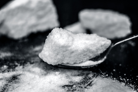 Common salt, Sodium chloride in a wooden scoop on wooden floor. Black and white