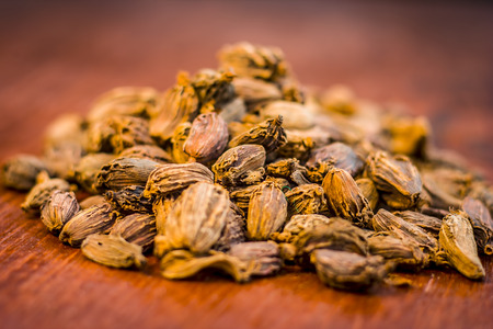Raw black cardamom on a brownish wooden surface. Stock Photo