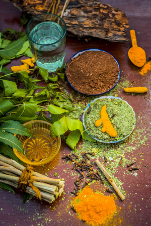 Close up of ingredients of ayurvedic treatment i.e neem,neem leaves,neem powder,bark,clove,turmeric,water.
