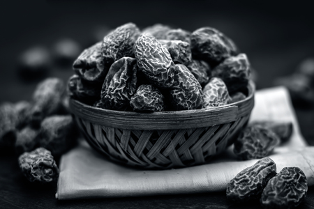 Close up of raw dried dates,Phoenix dactylifera in a traditional bowl on a wooden surface.