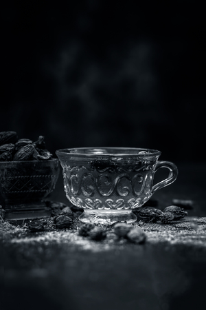 Close up of tea of Black cardamom with its powder and raw whole black cardamom.
