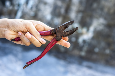 A hand holding  pliers. Stock Photo