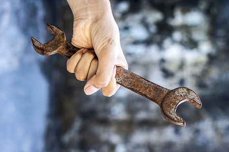 human hand holding old rusted spanner. Stock Photo